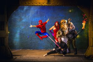 Performers on a stage wearing costumes of Spider-Man, Jessica Rabbit, Chewbacca, and Anakin Skywalker